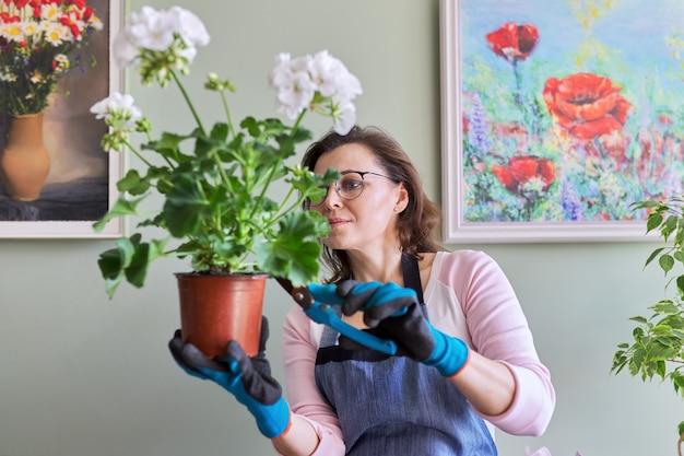 Femme s'occupant de fleurs en pot à la maison, enlève les feuilles du sécateur. passe-temps et loisirs, jardinage domestique, plante d'intérieur, jungle urbaine, concept d'amis en pot