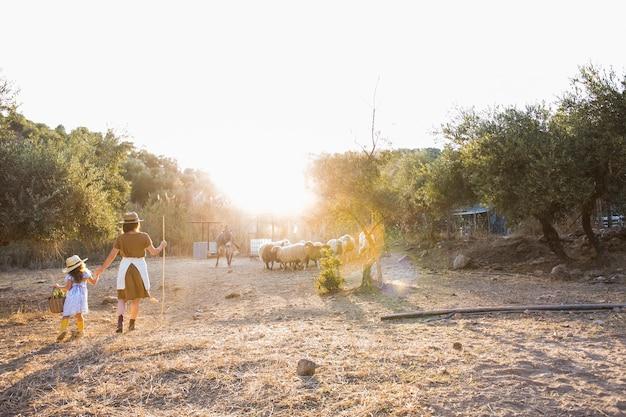 Femme avec sa fille marchant dans le champ avec des animaux