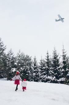 Femme et sa fille s'amusent dans la forêt d'hiver