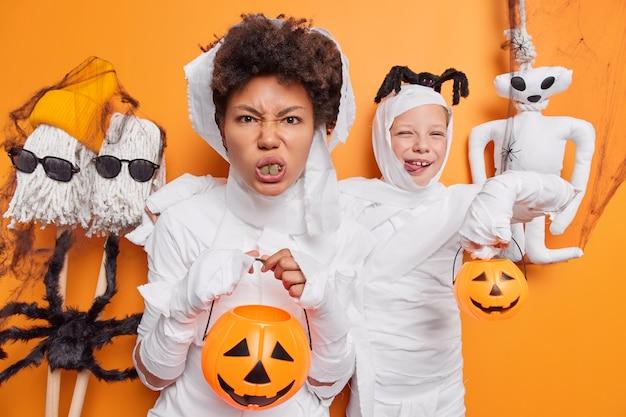 Femme et sa fille se préparent pour la fête d'halloween tenir des attributs de vacances portent des costumes de zombies blancs isolés sur un studio orange