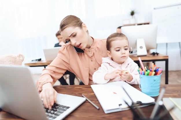 La femme avec sa fille vient travailler.