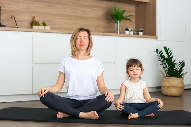Femme et sa jolie petite fille sont assis dans une position du lotus tout en faisant du yoga ensemble à la maison