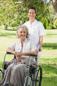 Femme avec sa mère assise dans une chaise roulante au parc