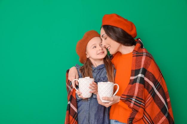 Femme et sa petite fille avec une boisson savoureuse au cacao sur fond de couleur