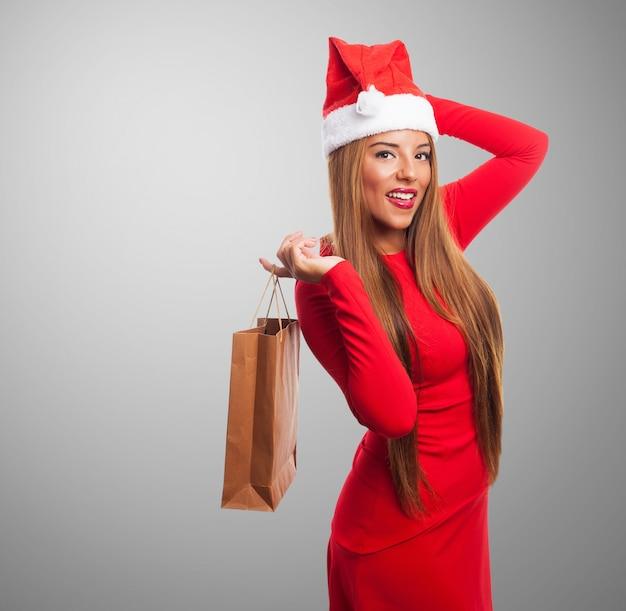 Femme avec un sac d'achat et le chapeau de père noël