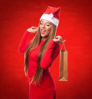 Femme avec un sac d'achat avec un chapeau de père noël