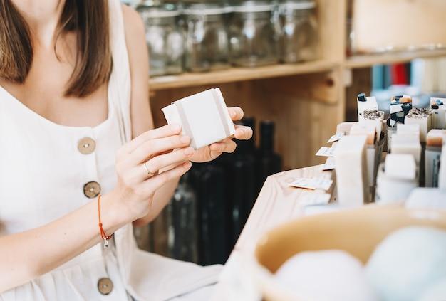Femme avec un sac en coton achetant des articles d'hygiène personnelle dans un magasin zéro déchet eco organic cosmetics