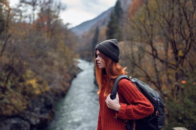 Femme avec sac à dos admire la rivière dans les montagnes
