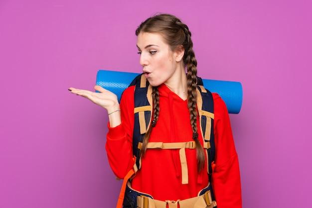 Femme avec sac à dos d'alpiniste sur mur isolé