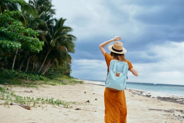 Une femme avec un sac à dos bleu dans une robe jaune et un chapeau se promène le long de l'océan le long du sable avec des palmiers