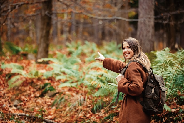 Femme avec un sac à dos dans la forêt d'automne
