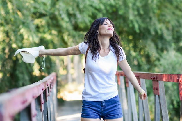 Femme avec sac à dos, debout sur un pont rural.