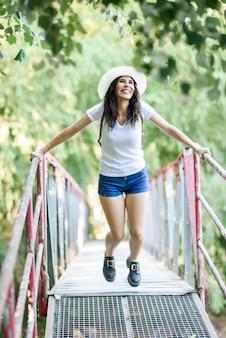 Femme avec sac à dos, debout sur un pont rural