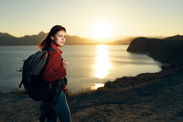 Femme avec sac à dos sur la nature notre voyage au coucher du soleil