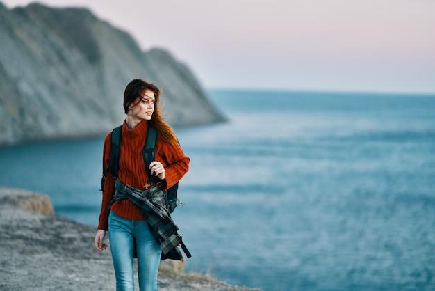 Femme avec sac à dos pull jeans voyage modèle de paysage de montagnes