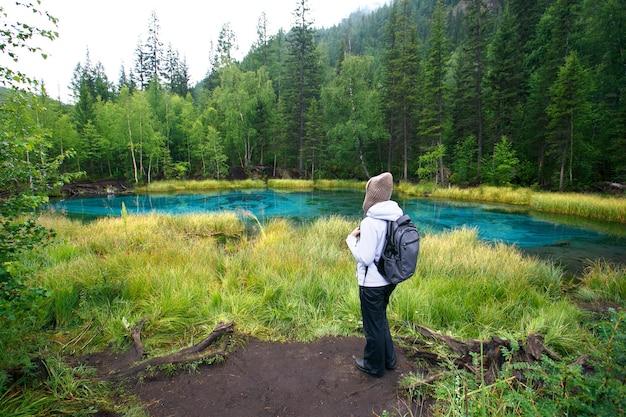 Femme avec sac à dos, randonnée, forêt et lac, concept aventure