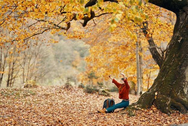 Femme avec un sac à dos sous un arbre dans le parc et la chute des feuilles paysage d'automne