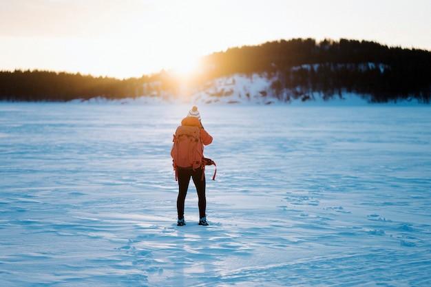 Femme avec un sac à dos trekking dans la neige