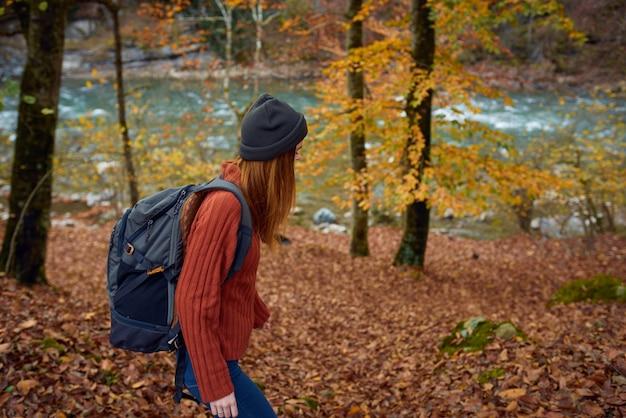 Femme avec sac à dos voyage tourisme forêt paysage parc rivière feuilles tombées vue latérale