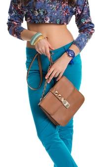 Femme avec sac marron. pantalon et crop top bleus. porte-monnaie en cuir de haute qualité. ensemble d'accessoires décontractés.