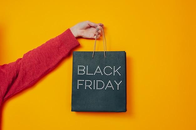 Femme avec sac noir. image de vendredi noir sur fond orange. sac à main et vendredi noir.