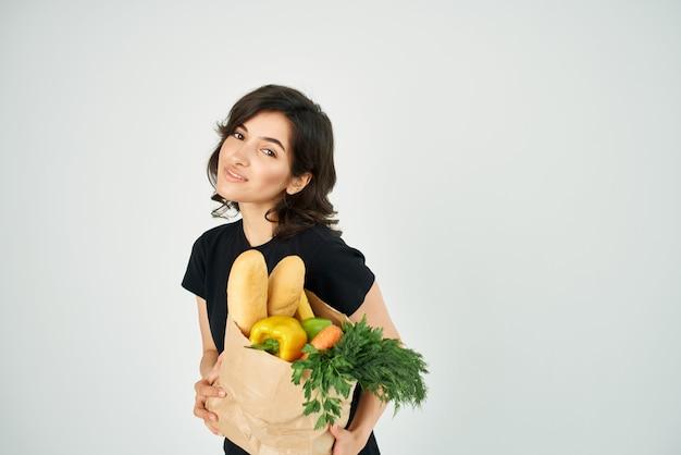 Femme avec un sac en papier d'épicerie dans les mains livrant des légumes des aliments sains. photo de haute qualité
