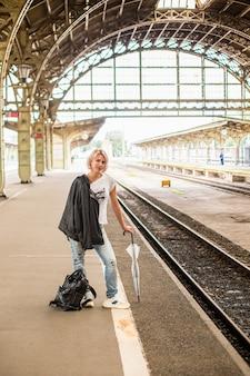 Une femme avec un sac et un parapluie dans une gare rétro