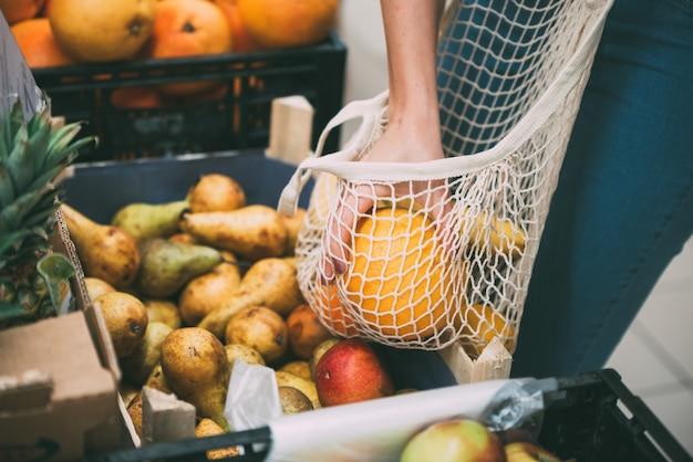 Femme avec un sac plein de légumes frais, shopping au magasin, concept zéro déchet