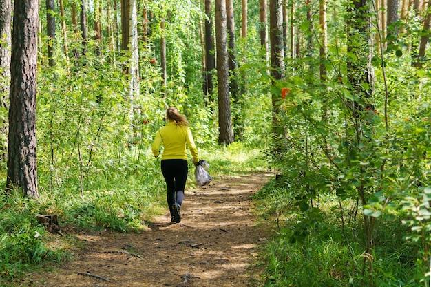 Une femme avec un sac poubelle court le long d'un sentier forestier pendant le plogging