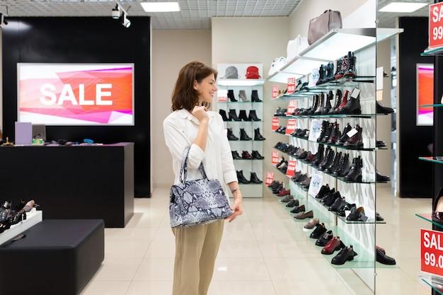 Femme avec sac de serpent regarde miroir, sourit et choisit des chaussures dans un grand centre commercial