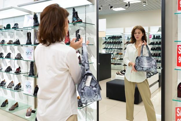 Femme avec sac de serpent regarde miroir, sourit et pense à son choix dans un grand centre commercial