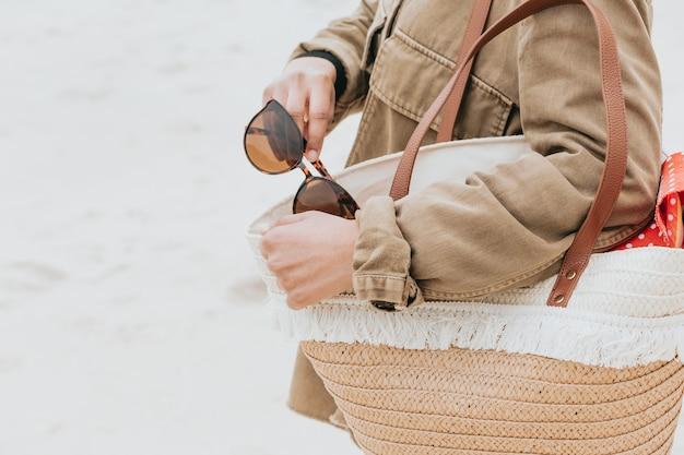 Femme avec un sac de soleil et une paire de lunettes de soleil à la plage, espace de copie, vacances et concept de vacances