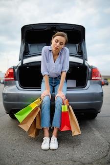 Femme avec des sacs au coffre ouvert sur le parking