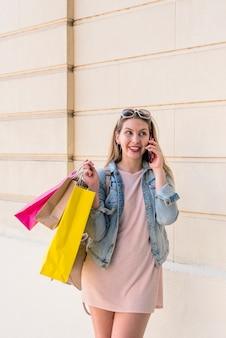 Femme avec des sacs colorés, parlant par téléphone au mur