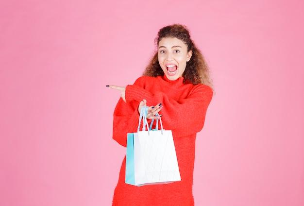 Femme avec des sacs colorés pointant vers le côté gauche.