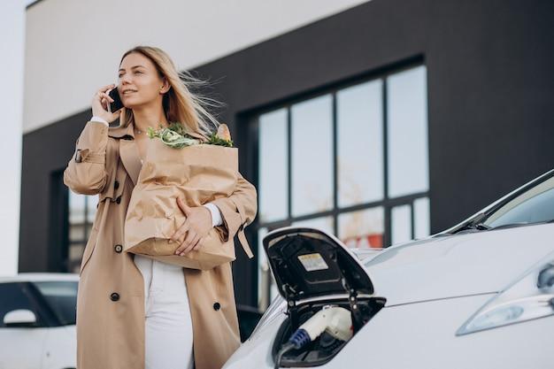 Femme avec des sacs de nourriture chargeant une voiture électrique