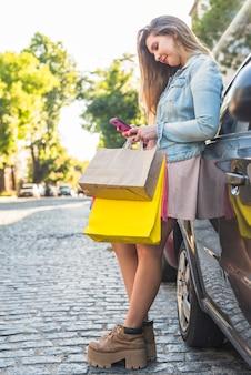 Femme avec des sacs à provisions à l'aide de smartphone en voiture