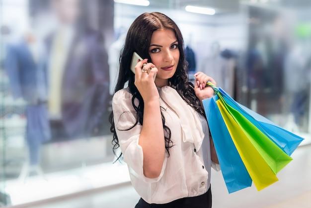 Femme avec des sacs à provisions appelant à quelqu'un dans un centre commercial