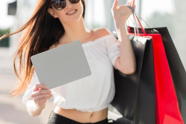 Femme avec des sacs à provisions et une bannière vide