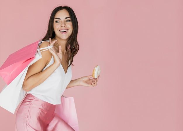 Femme avec des sacs à provisions et un beignet sur fond rose