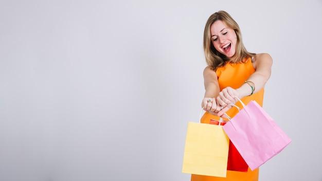 Femme avec des sacs à provisions et de l'espace sur la gauche