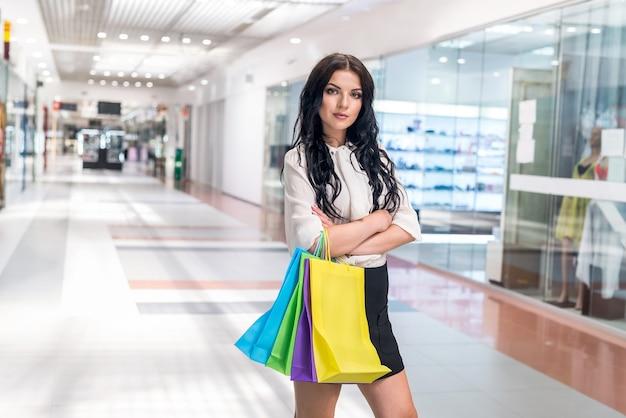 Femme avec des sacs à provisions posant dans l'allée du centre commercial