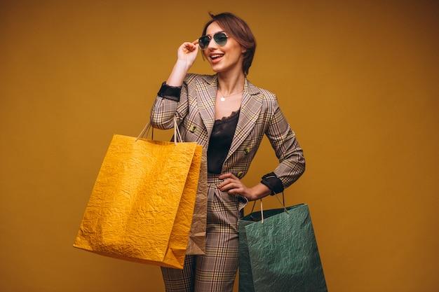 Femme avec des sacs à provisions en studio sur fond jaune isolé