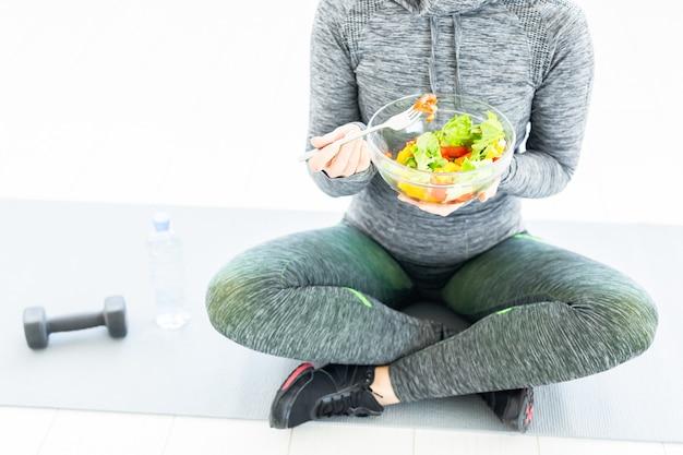 Femme avec salade et un haltère assis sur le sol