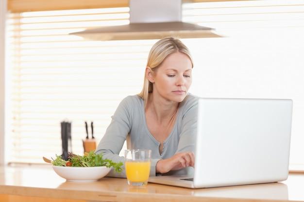 Femme avec salade et orange travaillant sur ordinateur portable dans la cuisine