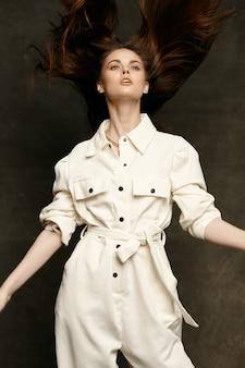 Femme en salopette sur un fond sombre étend ses bras sur les côtés vue rapprochée en gros plan