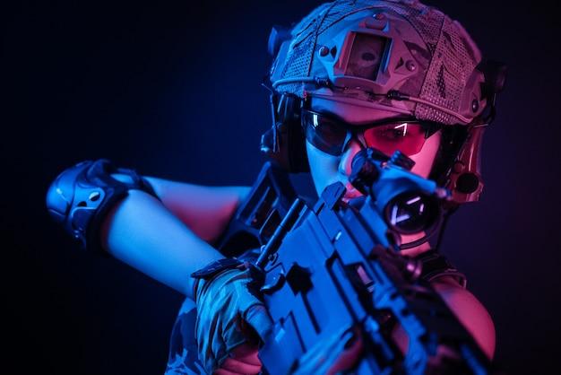 Femme en salopette militaire airsoft posant avec une arme à feu dans ses mains sur un mur sombre dans la brume en néon
