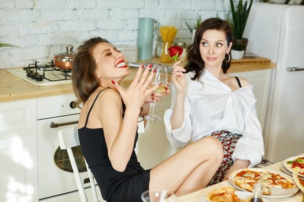Femme sans complexes mange de la pizza et des spaghettis à la maison. joie et rire sur le visage de la femme