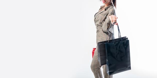 Femme sans nom avec des sacs noirs et rouges. concept de magasinage de vacances. technique mixte