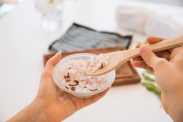 Femme sans visage avec une cuillère et du sel rose dans un bol